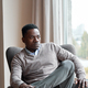 Confident stylish black man sitting in chair at home looking through window. - PhotoDune Item for Sale