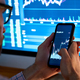 Trader using mobile phone app analytics for stock trading graph data analysis. - PhotoDune Item for Sale