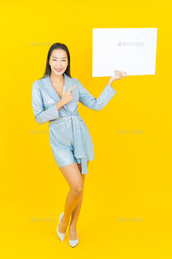 Portrait beautiful young asian woman smile with empty white billboard - Stock Photo - Images
