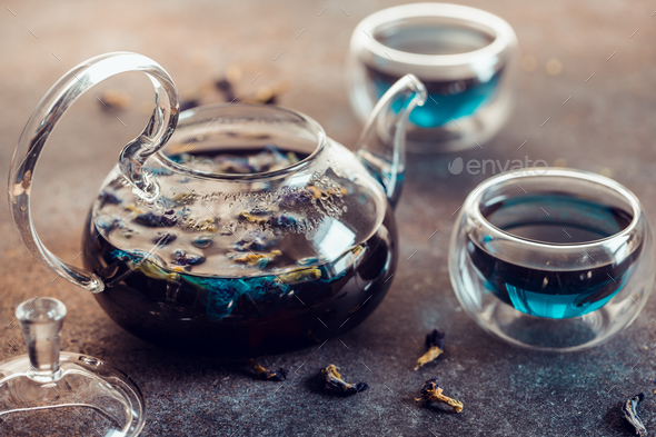 Thai Butterfly pea tea in a glass teapot and cups on a table. - Stock Photo - Images