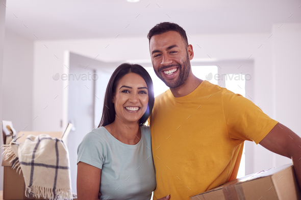 Portrait Of Couple Carrying Boxes Through Front Door Of New Home On Moving Day - Stock Photo - Images