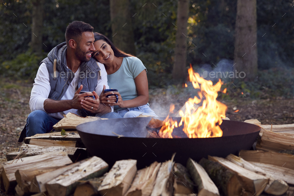 Romantic Couple Camping Sitting By Bonfire In Fire Bowl With Hot Drinks - Stock Photo - Images