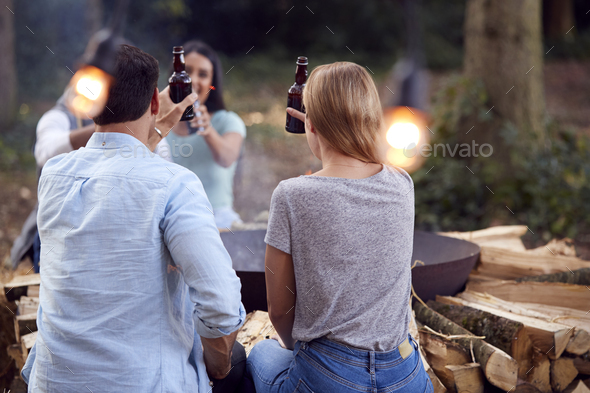 Group Of Friends Camping Sitting By Bonfire In Fire Bowl Celebrating And Drinking Beer Together - Stock Photo - Images