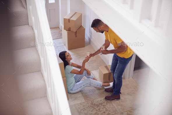 Couple Celebrating With Champagne Sitting On Floor Of New Home On Moving Day - Stock Photo - Images