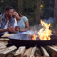 Romantic Couple Camping Sitting By Bonfire In Fire Bowl With Hot Drinks - PhotoDune Item for Sale