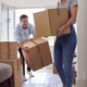Excited Couple Carrying Boxes Through Front Door Of New Home On Moving Day - PhotoDune Item for Sale