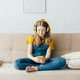 A cute redhead teenage girl  sits on the couch at home and smiling looks into the mobile phone. - PhotoDune Item for Sale