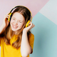 Funny redhead girl in yellow t-shirt dancing on colorful  wall background,  studio portrait. - PhotoDune Item for Sale