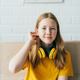Portrait of a cute redhead schoolgirl in a yellow T-shirt with wireless headphones. - PhotoDune Item for Sale