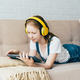 A teenage schoolgirl lying on the couch plays a digital tablet and listens with headphones. - PhotoDune Item for Sale