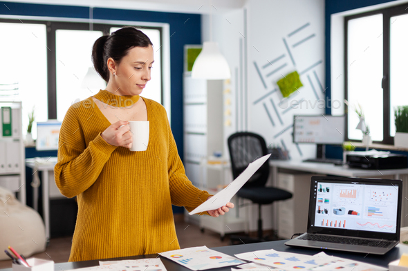 Confident business woman holding documents with statistics - Stock Photo - Images