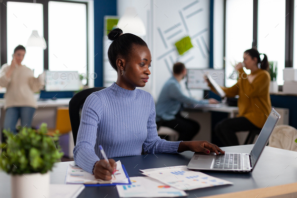 African businesswoman taking notes on clipboard analysing statistics - Stock Photo - Images