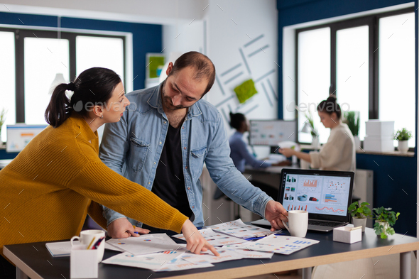 Woman in start up office explaining charts to executive businessman - Stock Photo - Images