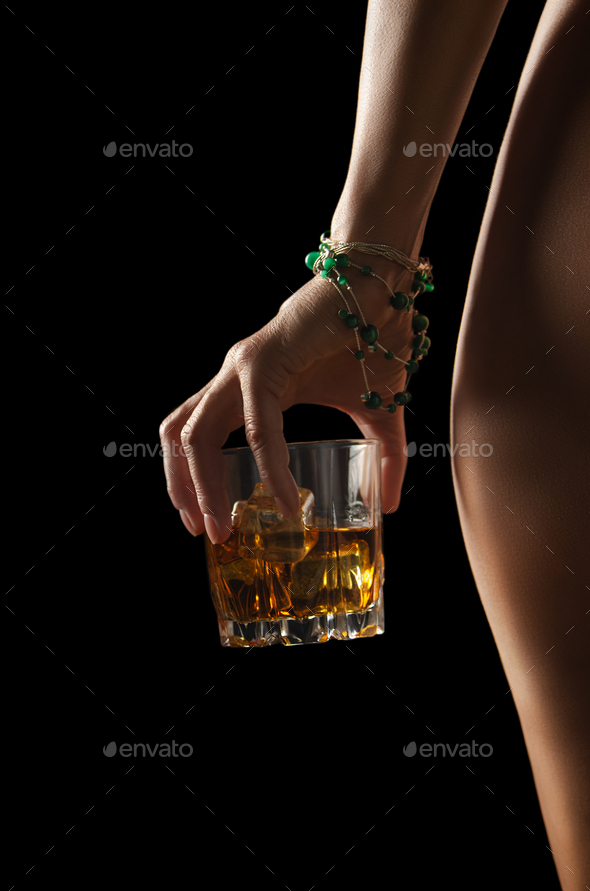 Caucasian model holds glass of whiskey with icecubes in her hand - Stock Photo - Images