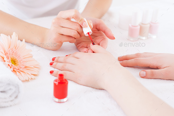 Manicurist in action. Close-up of manicurist doing red manicure to female customer - Stock Photo - Images