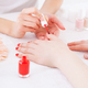 Manicurist in action. Close-up of manicurist doing red manicure to female customer - PhotoDune Item for Sale
