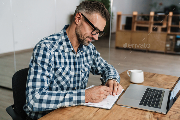 Pleased grey man writing down notes while working with laptop - Stock Photo - Images