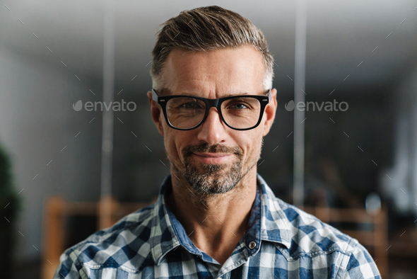 Serious white-haired man looking at camera while standing - Stock Photo - Images