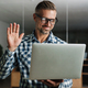 Smiling handsome man waving hand while working with laptop - PhotoDune Item for Sale