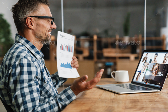 Happy grey man showing graphics while taking conference call on laptop - Stock Photo - Images
