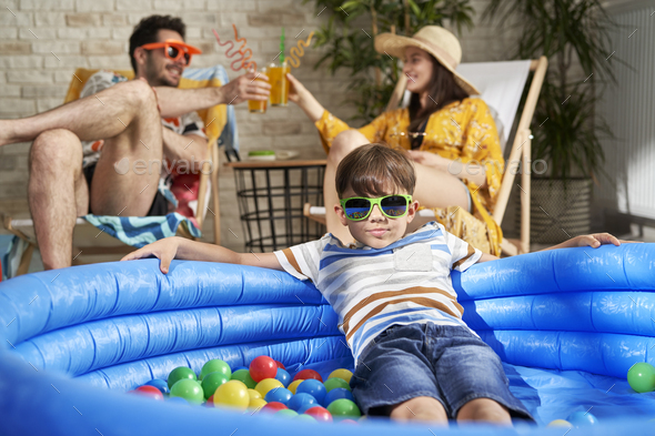 Portrait of boy in swimming pool and parents drinking drink - Stock Photo - Images