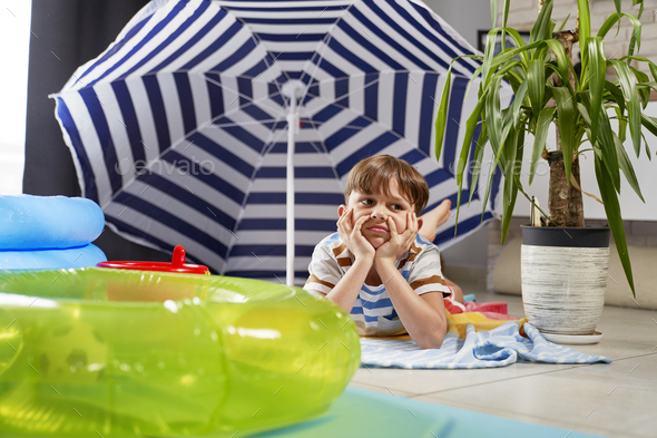 Bored boy spending his beach vacation at home - Stock Photo - Images