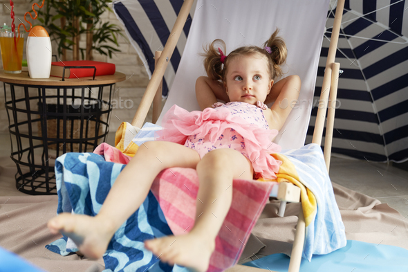 Relaxed little girl lying outdoor chair in swimwear - Stock Photo - Images