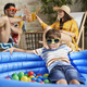 Portrait of boy in swimming pool and parents drinking drink - PhotoDune Item for Sale