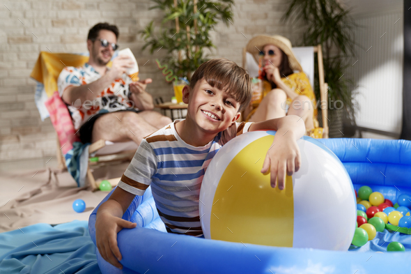 Portrait of relaxed boy in an inflatable ball pool at home - Stock Photo - Images