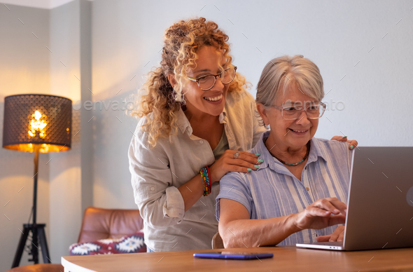 Beautiful blonde adult daughter teaching her mother how to use the network with digital laptop - Stock Photo - Images