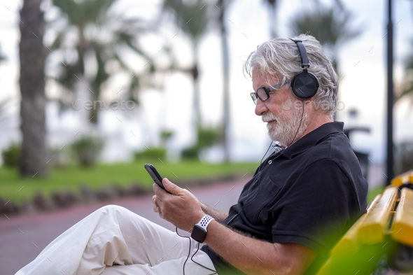 Portrait of senior white-haired man sitting in a bench and listening to music with headphones - Stock Photo - Images