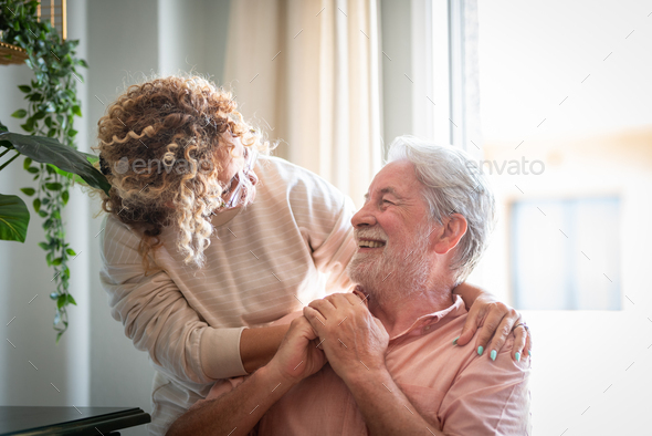 Portrait of adult woman lovingly caring for her elderly father at home while spending time together - Stock Photo - Images