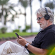 Portrait of senior white-haired man sitting in a bench and listening to music with headphones - PhotoDune Item for Sale