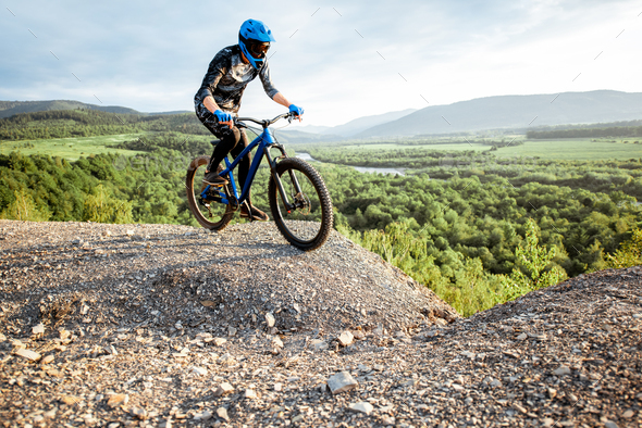 Cyclist riding on the rocky mountains - Stock Photo - Images