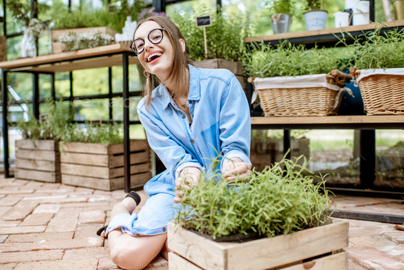 Woman with herbs in the greenhouse - Stock Photo - Images