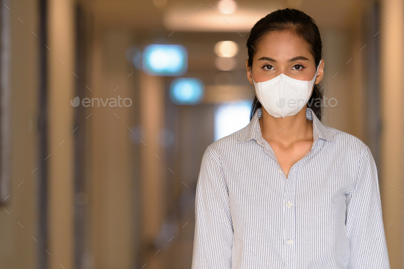 Asian woman wearing face mask to protect from coronavirus Covid-19 at apartment hallway - Stock Photo - Images