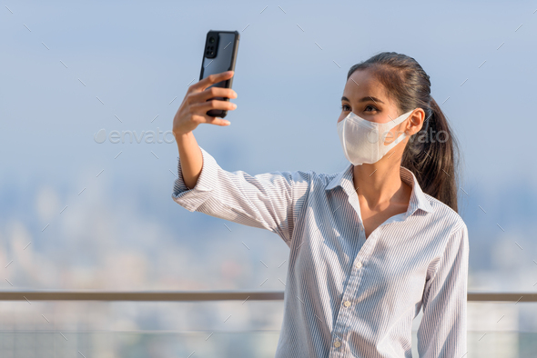 Woman influencer wearing face mask while using phone and taking selfie or vlogging - Stock Photo - Images