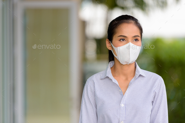 Asian woman wearing face mask to protect from coronavirus Covid-19 while thinking - Stock Photo - Images