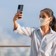 Woman influencer wearing face mask while using phone and taking selfie or vlogging - PhotoDune Item for Sale