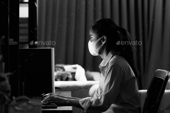 Woman wearing face mask to protect from coronavirus Covid-19 while working at home late at night - Stock Photo - Images