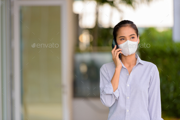 Woman wearing face mask to protect from coronavirus Covid-19 while talking on phone - Stock Photo - Images