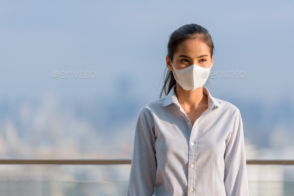 Asian woman wearing face mask to protect from coronavirus Covid-19 at rooftop outdoors while - Stock Photo - Images