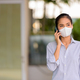 Woman wearing face mask to protect from coronavirus Covid-19 while talking on phone - PhotoDune Item for Sale