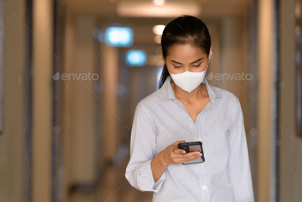 Asian woman wearing face mask to protect from coronavirus Covid-19 at apartment hallway while using - Stock Photo - Images