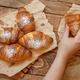 Hand taking french fresh crusty croissant from a wooden table - PhotoDune Item for Sale