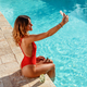 Young woman taking selfie on the border of a swimming pool - PhotoDune Item for Sale