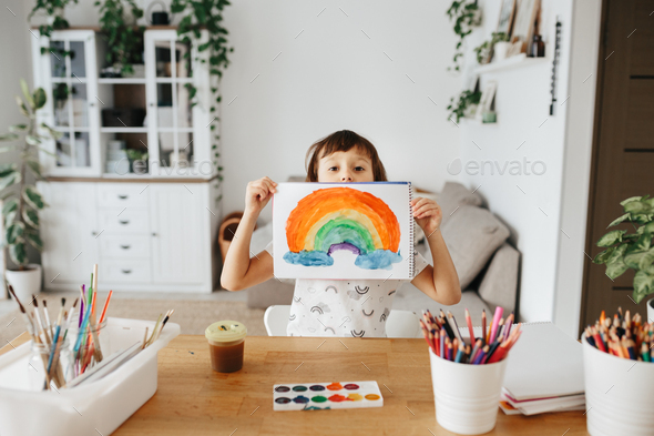 Kids painting watercolor rainbows at table at home - Stock Photo - Images