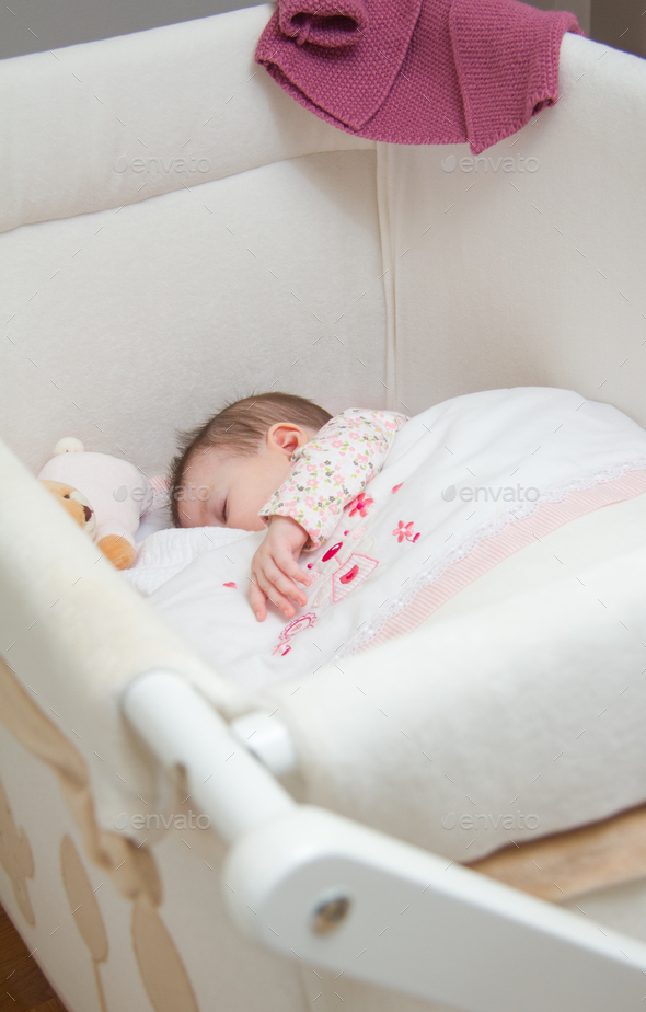 Baby girl sleeping in a cot with pacifier and toy - Stock Photo - Images