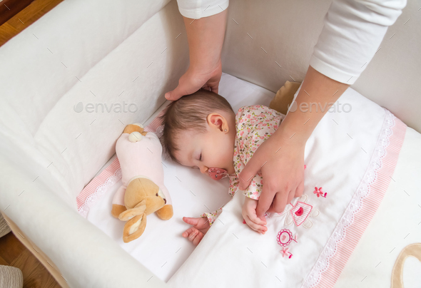 Hands of mother caressing her baby girl sleeping - Stock Photo - Images