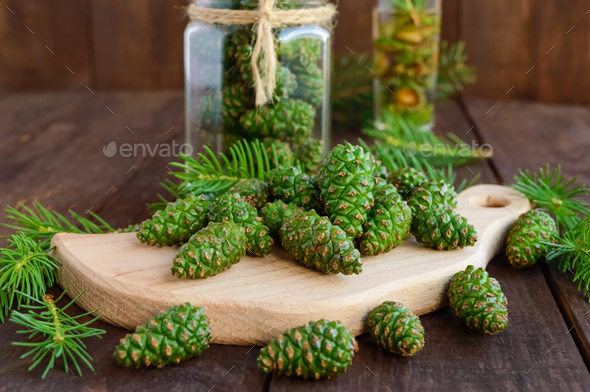 Young green fir cones on the wooden background. For making medicinal infusion. - Stock Photo - Images